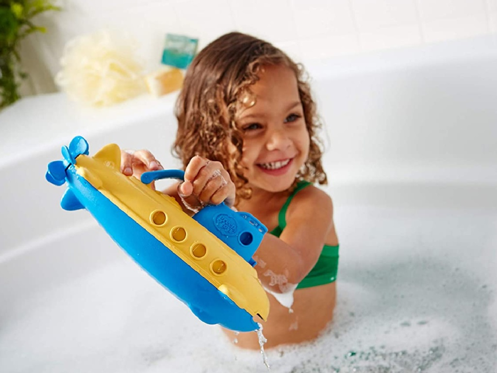 little girl playing in bubble bath with submarine toy