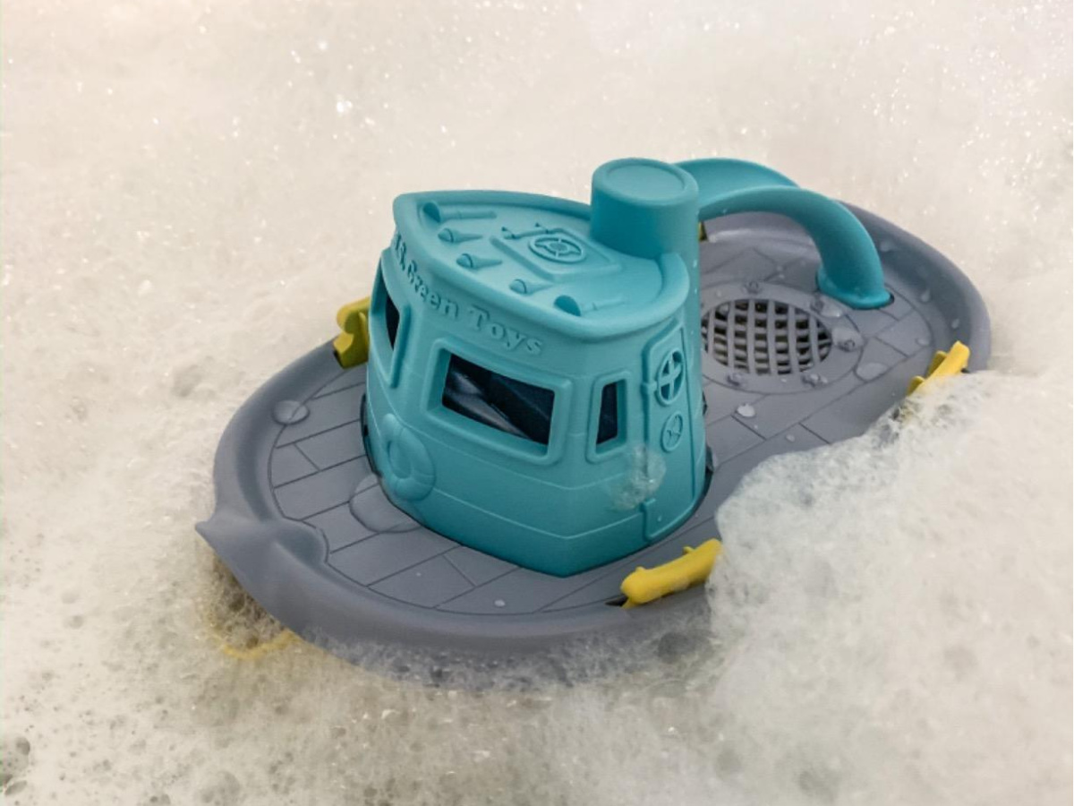 tugboat toy floating on bubbles in bathtub