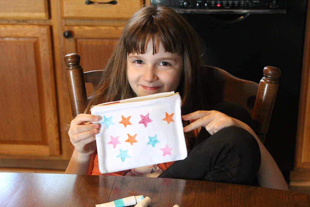 little girl pointing at stamped pouch