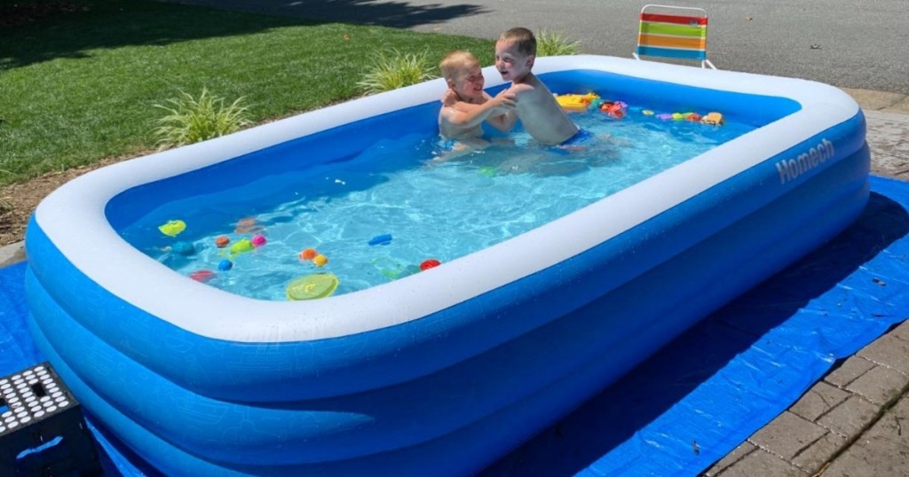 2 boys swimming in inflatable pool