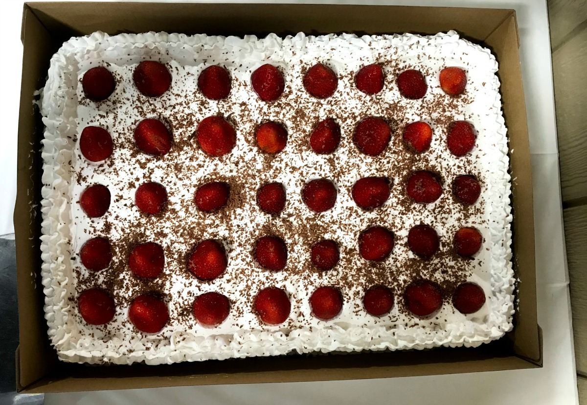 frosted cake decorated with fresh strawberries