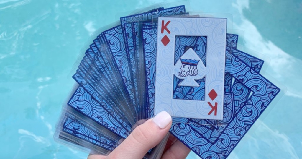 hand holding waterproof playing cards by pool