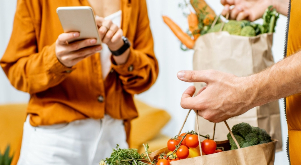 person holding phone with other persons hands holding brown bags of groceries