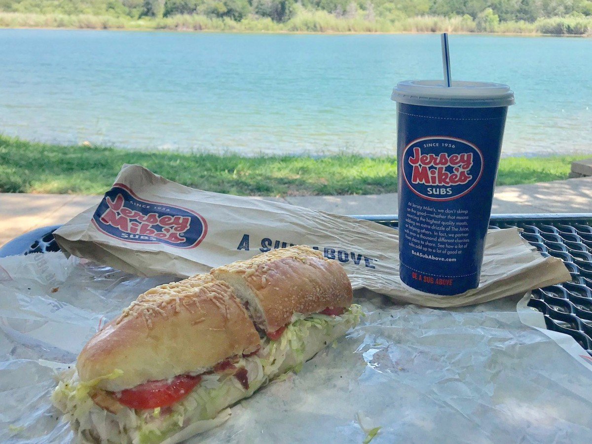 sub and blue cup near a lake