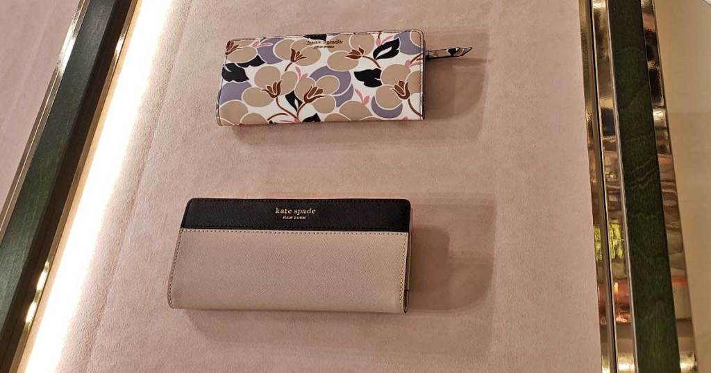 kate spade large wallets on display in store on felt table