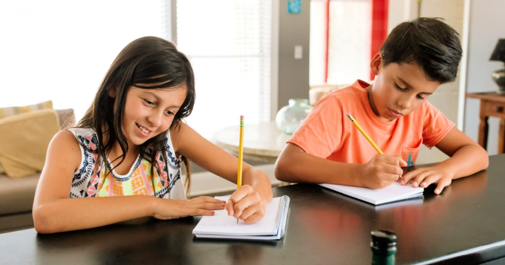 kids writing on notebook with a Ticonderoga pencil