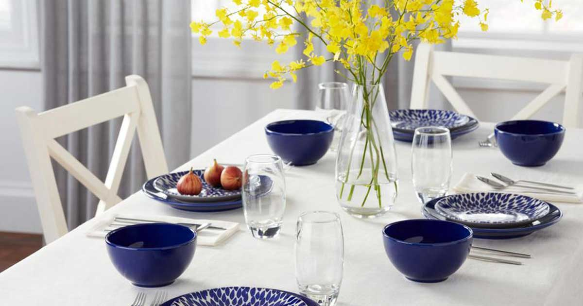 table in a dining room set with blue plates and glasses