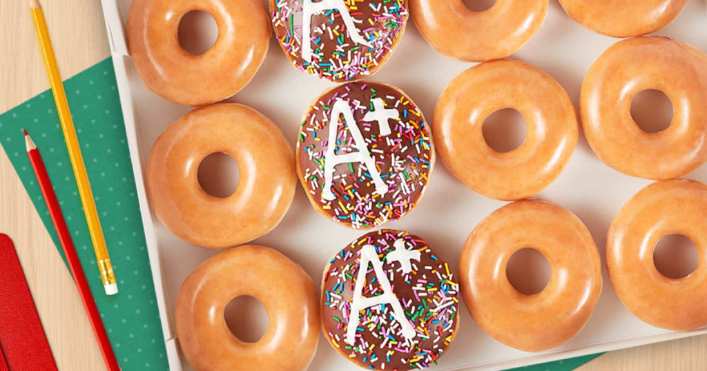 donuts in box with some decorated with the letter A on them