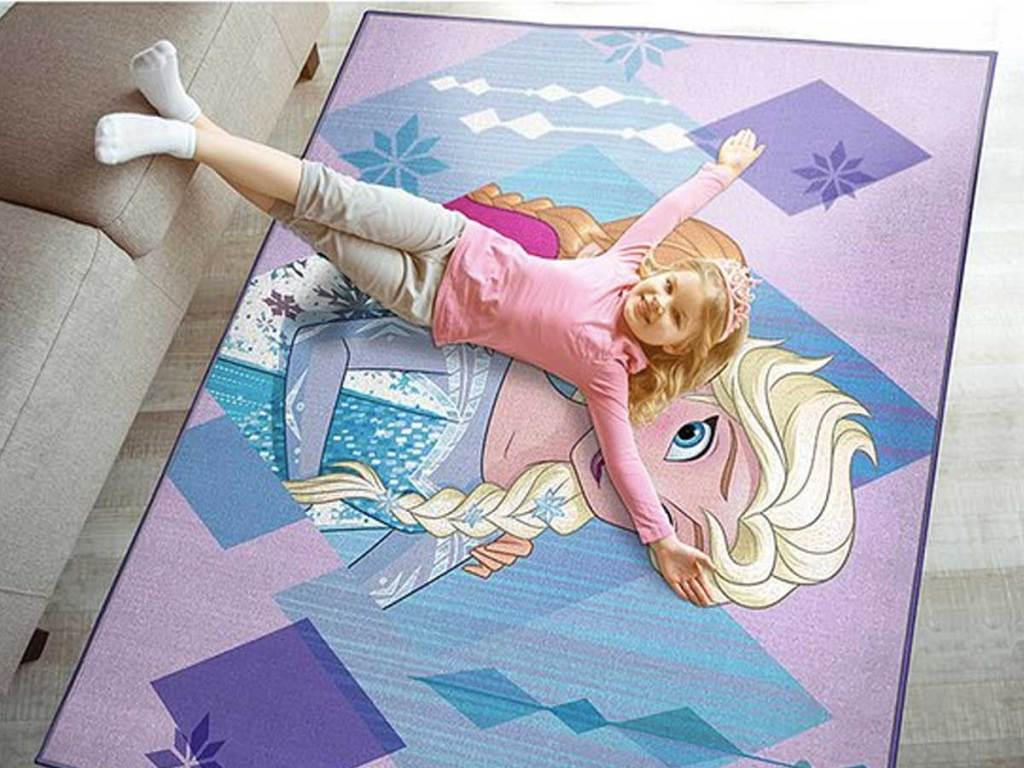 little girl laying on a rug with a disney character
