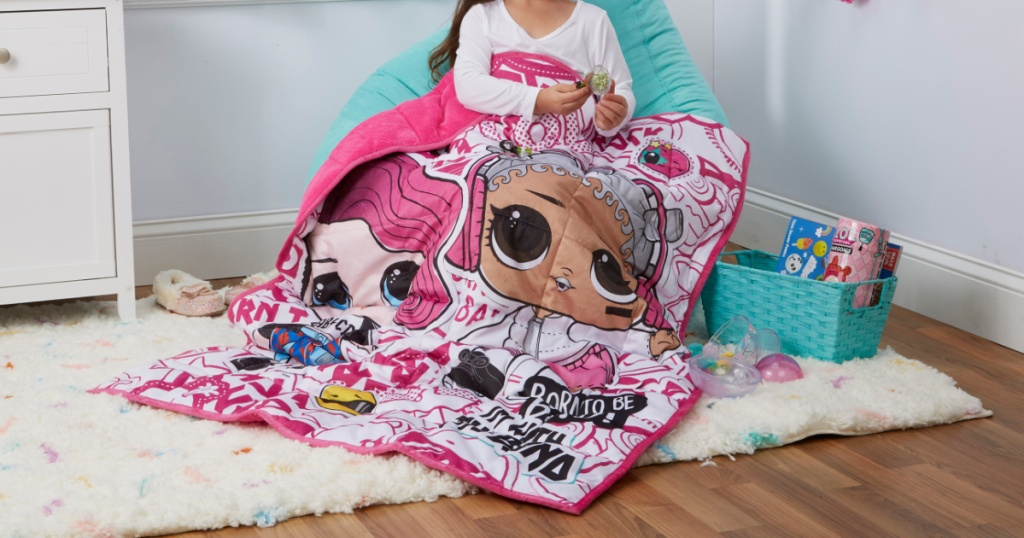 little girl sitting on chair with lol weighted blanket