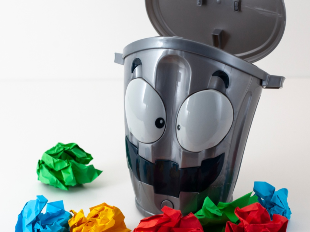 silver trash can with face on it surrounded by colored balls of paper