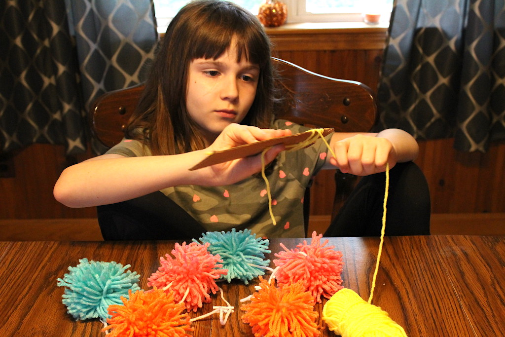 child making pom pom garland at table