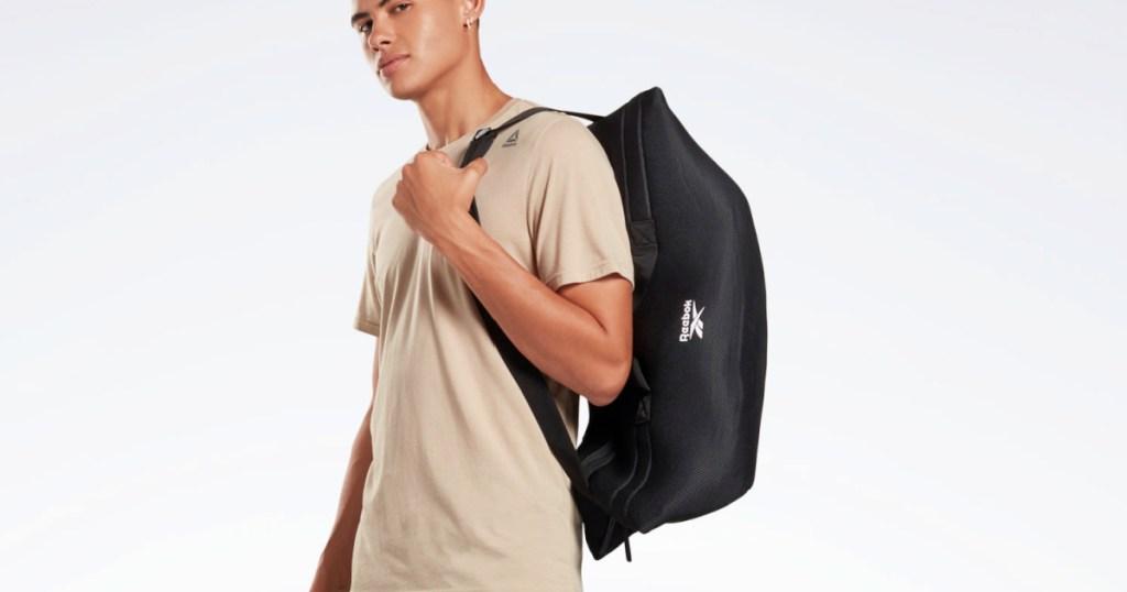 man holding a Reebok Training Supply Bag