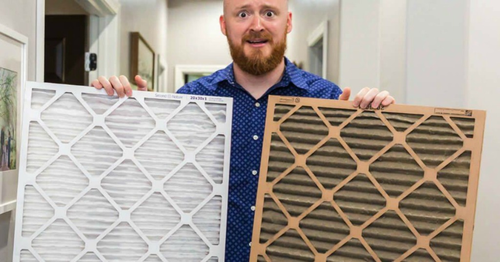 man holding two air filters in house