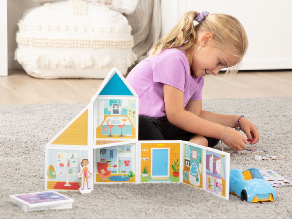 little girl playing with small toys to build a house