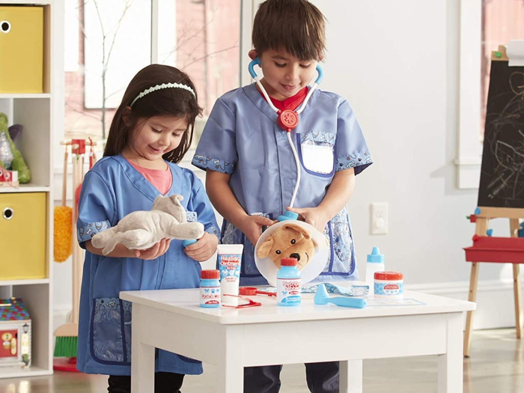 2 kids playing with stuffed animals like they are being vets