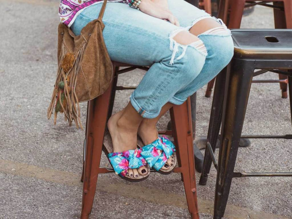 woman sitting on a stool outside wearing cute sandals