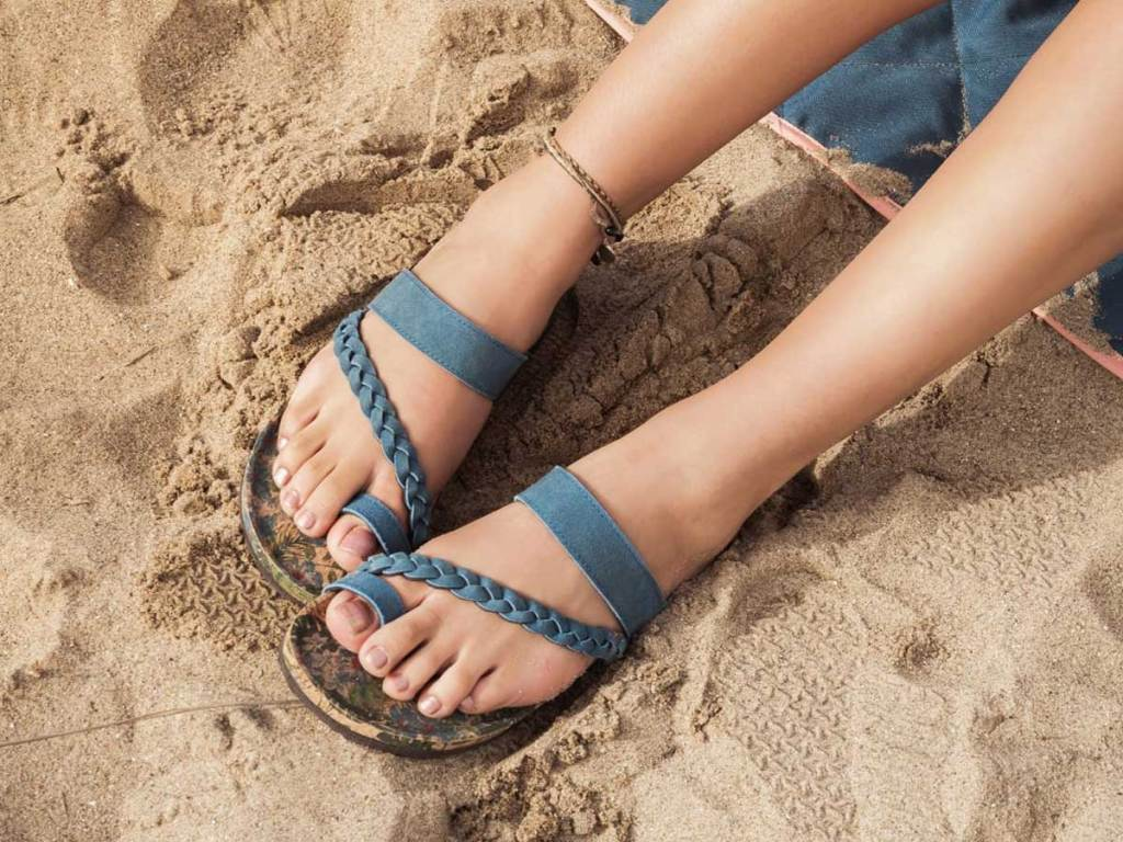 women wearing blue sandals in the sand