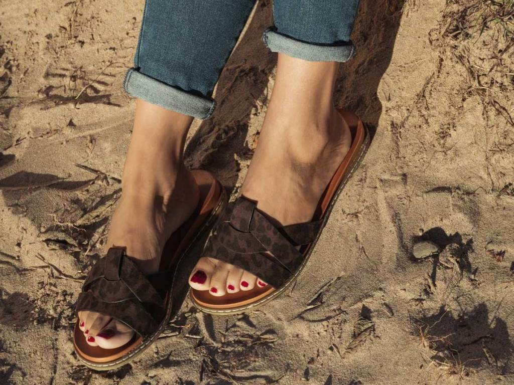 woman wearing brown sandals in the sand
