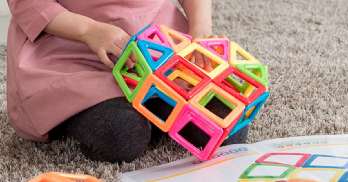 girl playing with magnetic building pieces