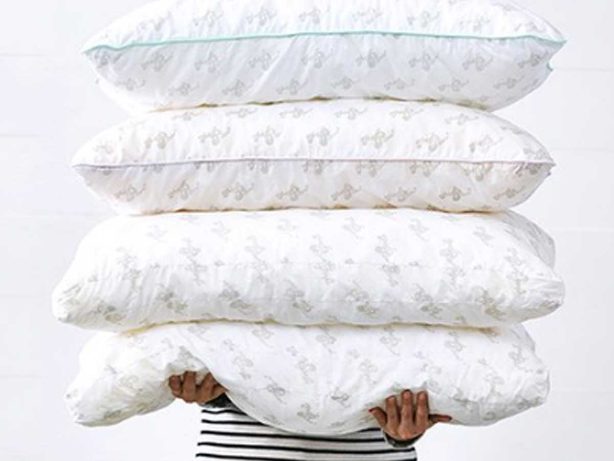 someone holding a stack of four pillows