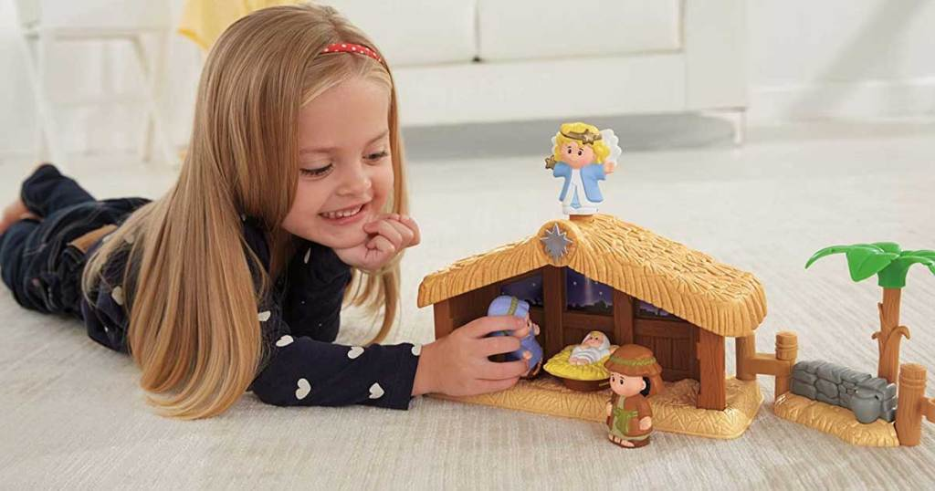little girl playing with a fisher price nativity set