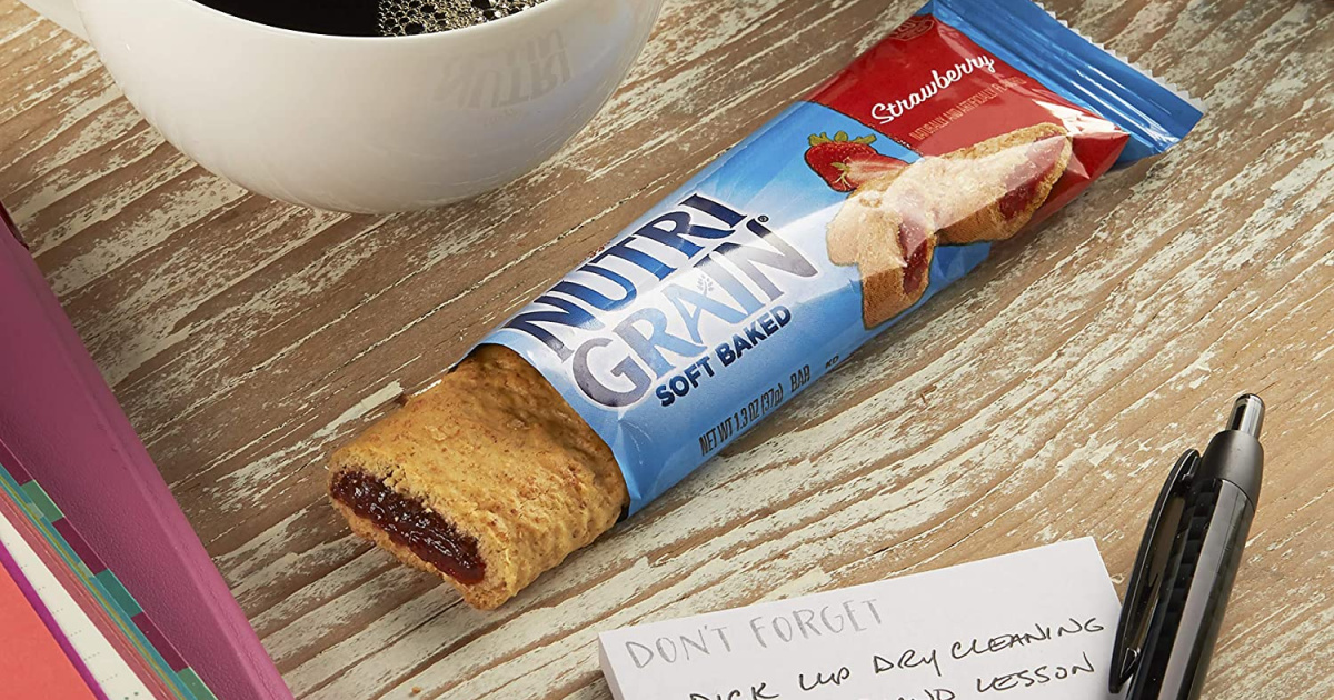 breakfast bar open on desk next to coffee and pen with list