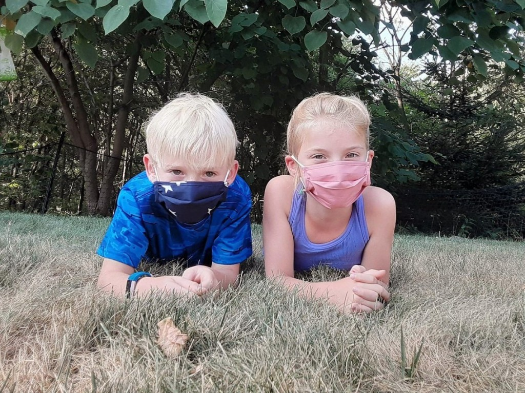 two kids lying on grass wearing face masks