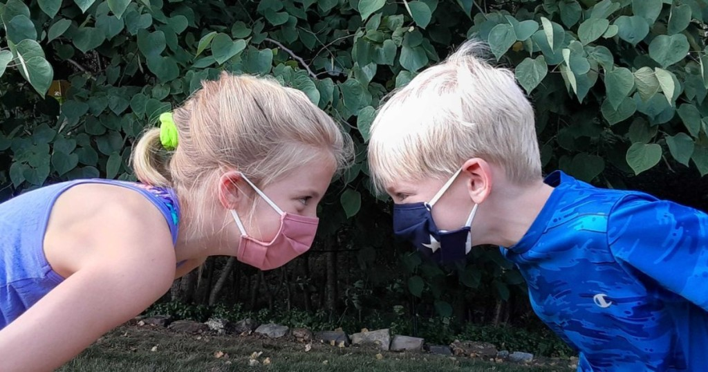 2 kids facing each other wearing face masks
