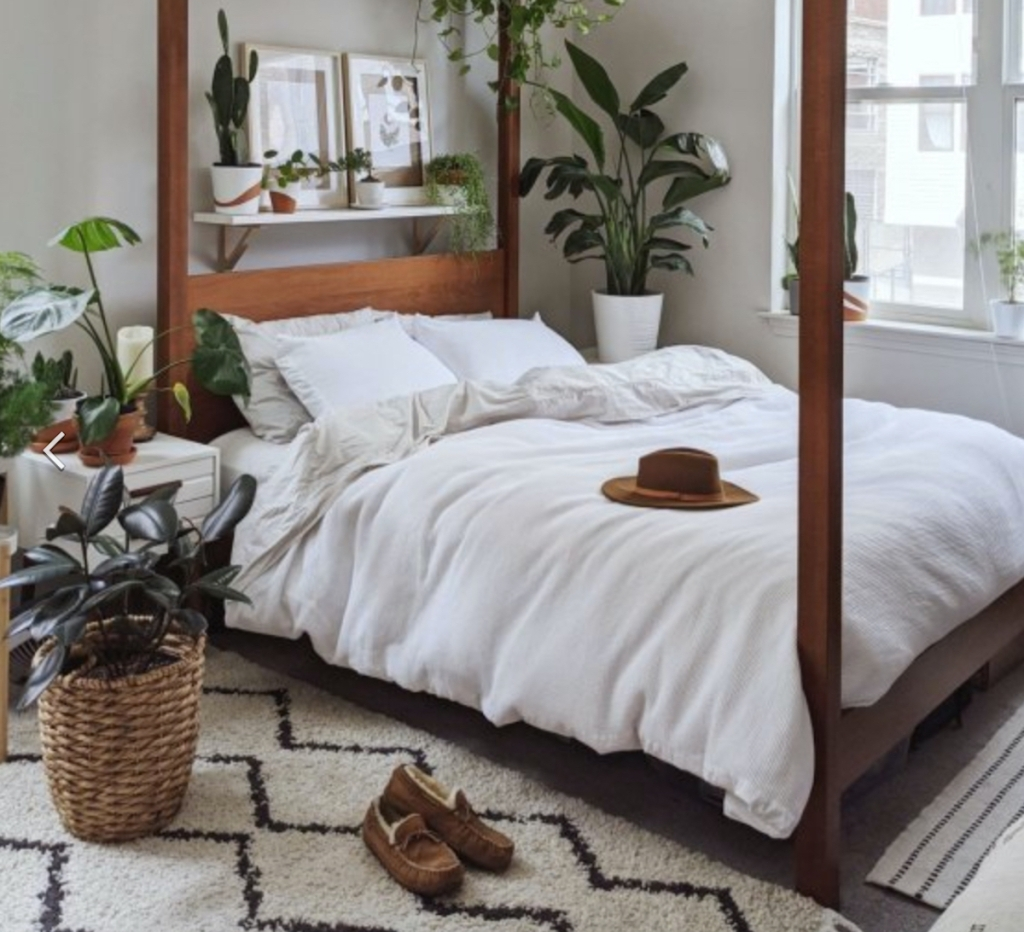 wood canopy bed with tons of green plants