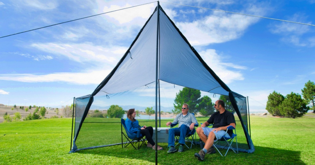 people sitting under a Ozark Trail Tarp Shelter with UV Protection and Roll-up Screen Walls