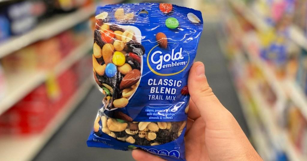 person holding a bag of gold emblem classic blend trail mix