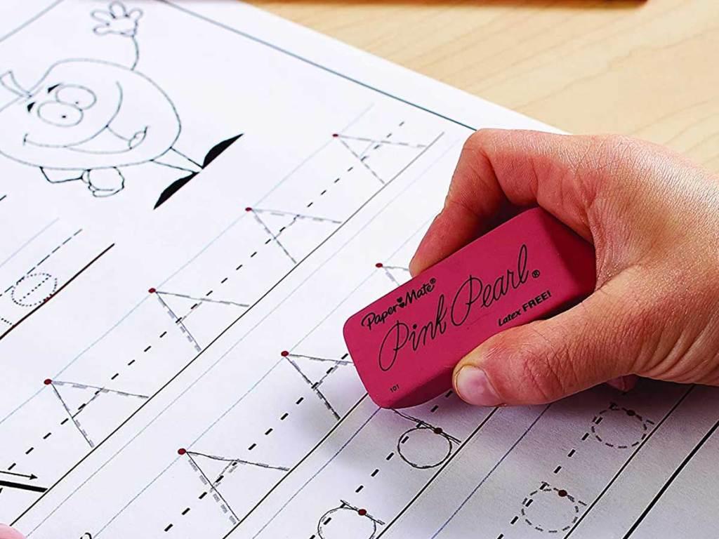 papermate pink pearl eraser being held to erase grade school alphabet paper