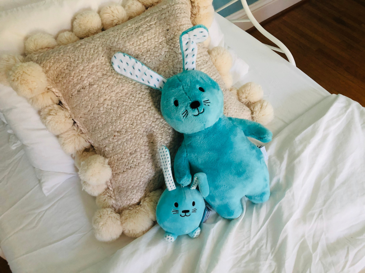 Blue bunny plush pal and clippable bunny on white bed