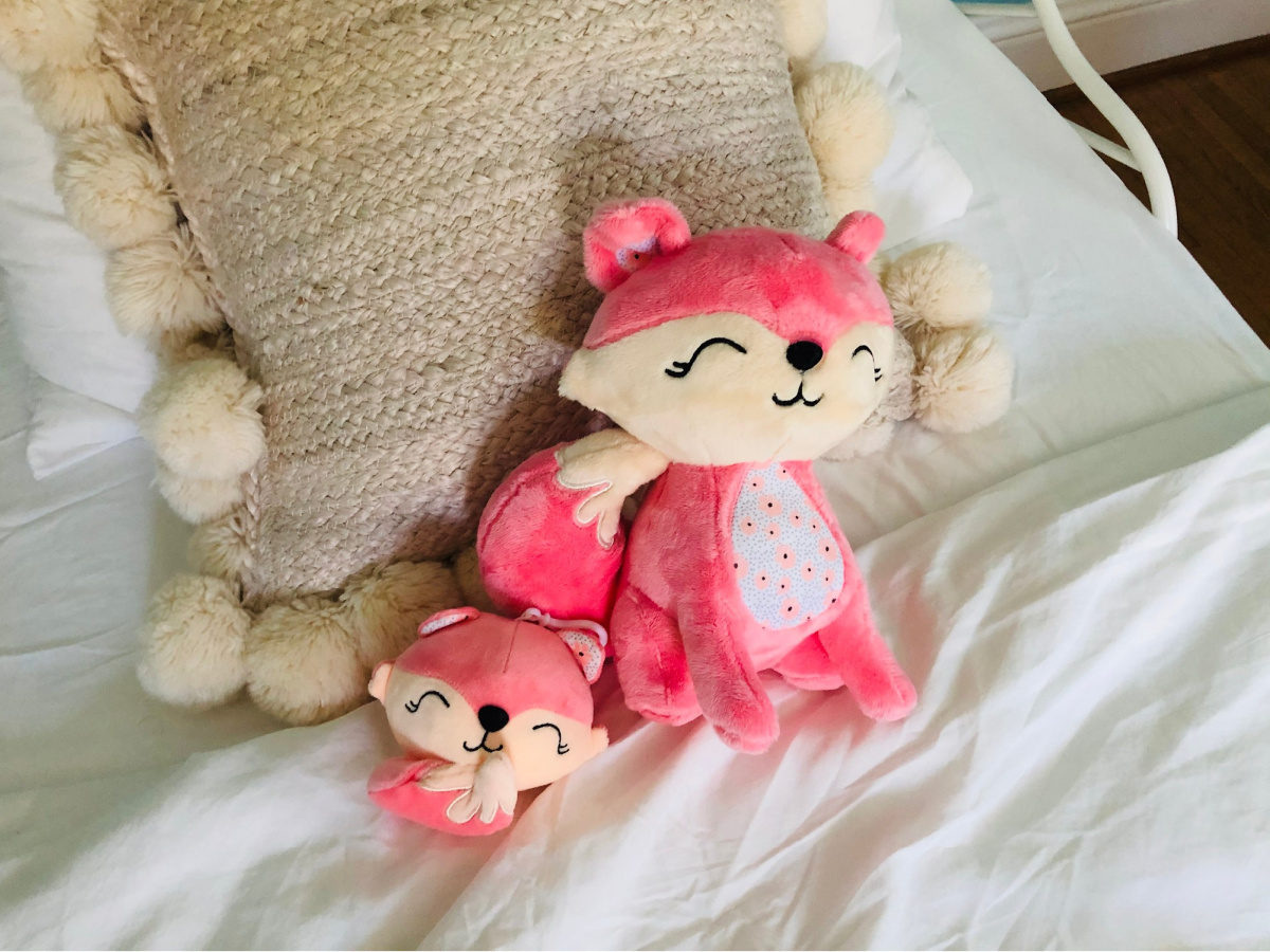 pink clippable fox and regular fox on white bed