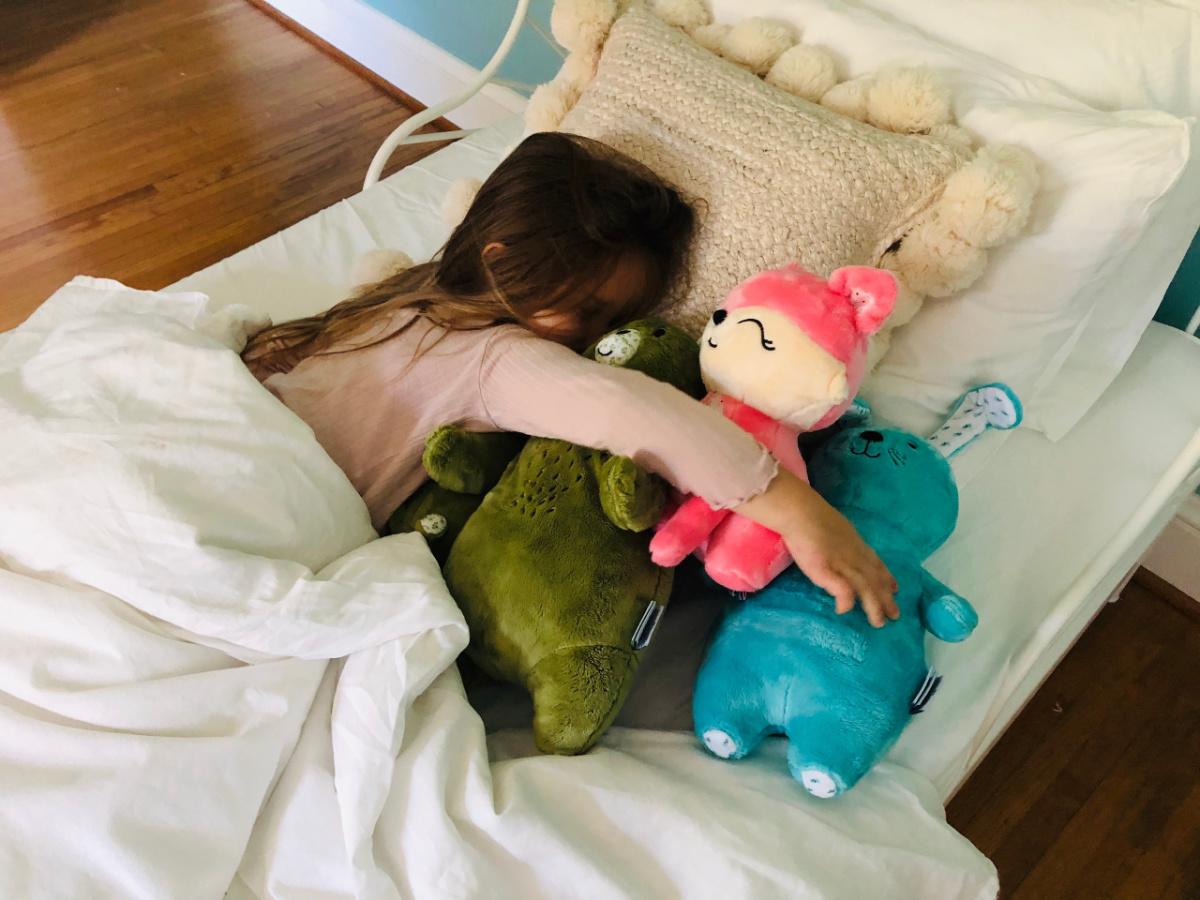 little girl sleeping with three Aroma plush pals