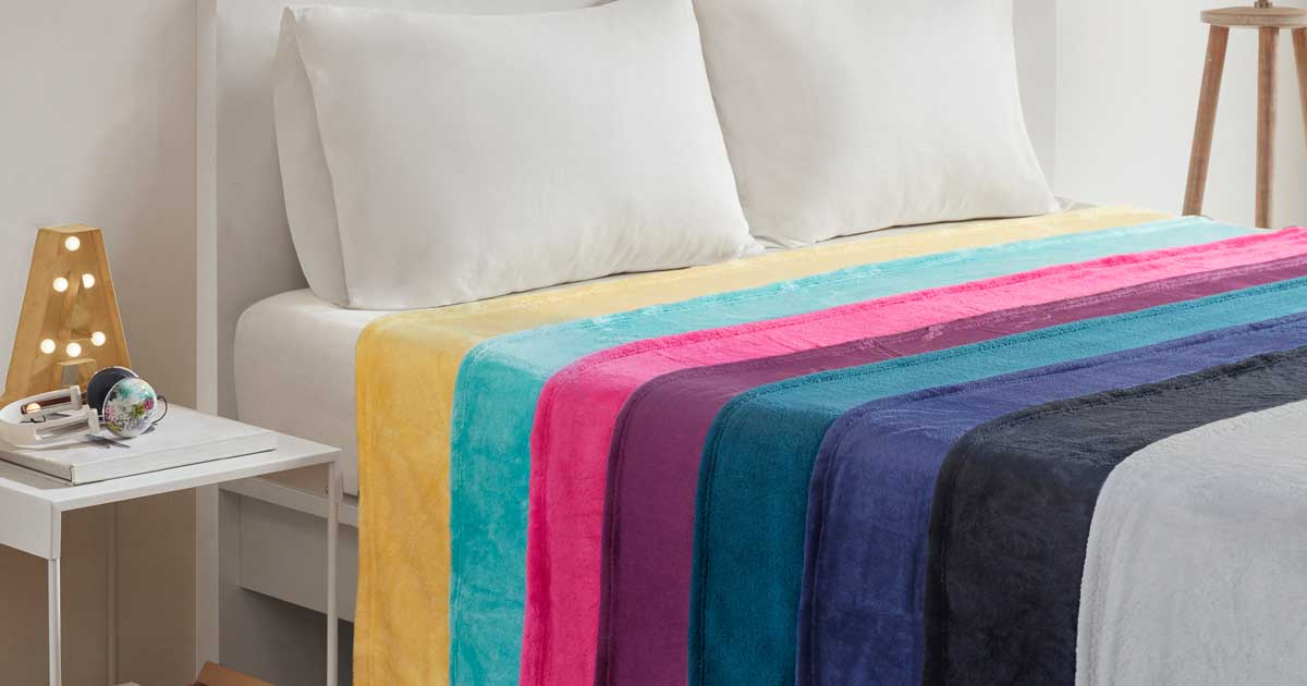 multi colored blankets spread onto a bed