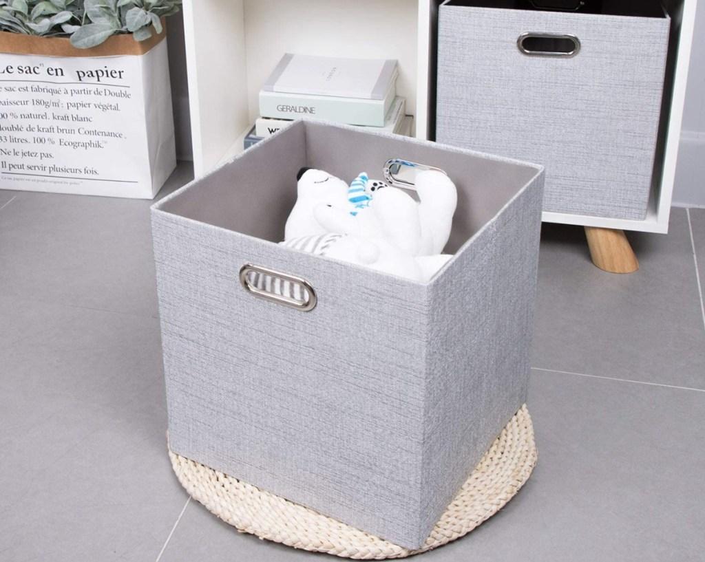 foldable gray storage bin with a teddy bear inside