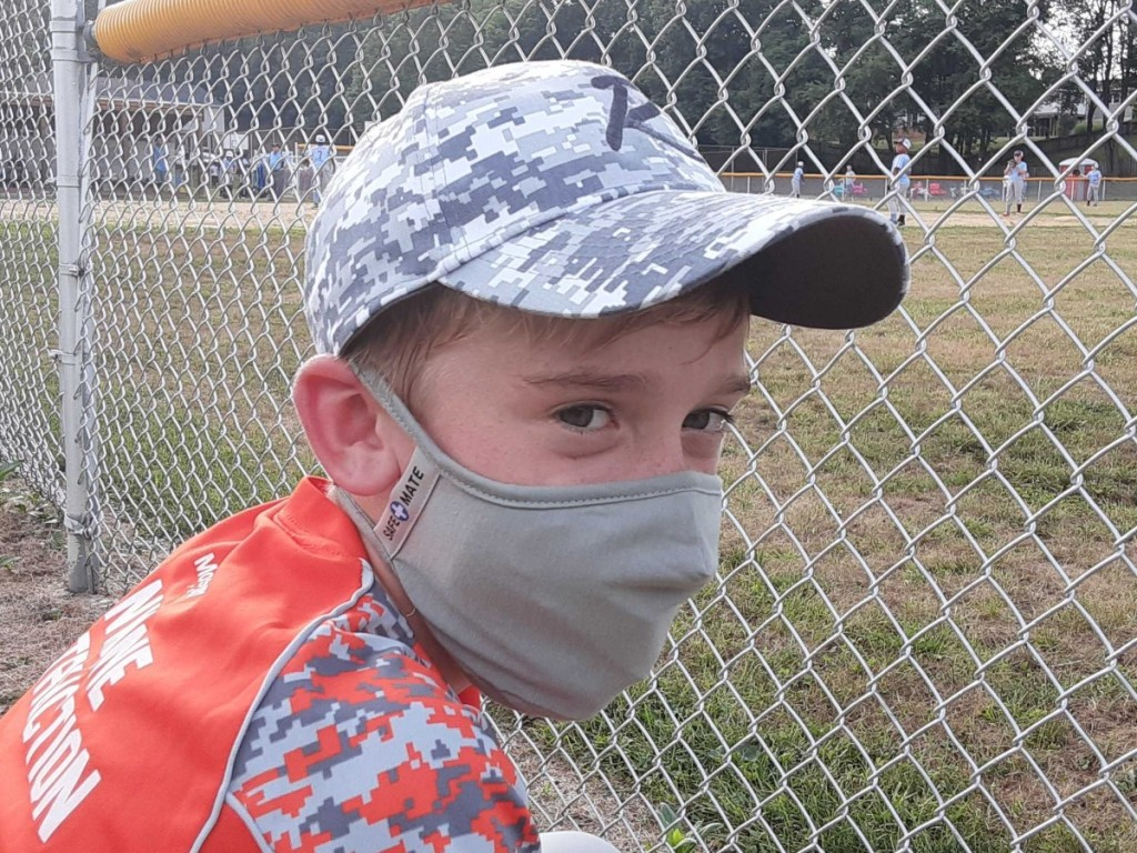 boy wearing baseball hat and gray facemask