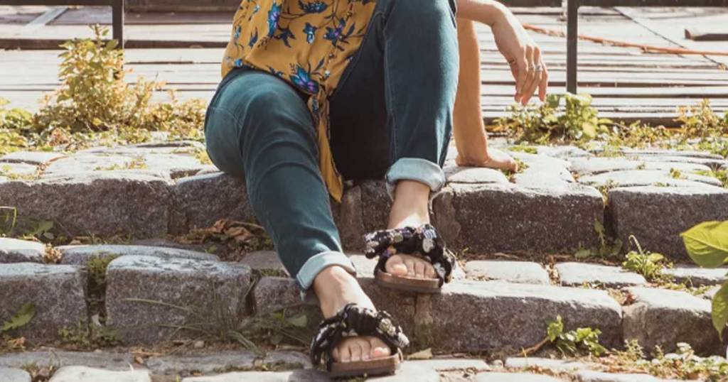 woman wearing big bow sandals on steps outside