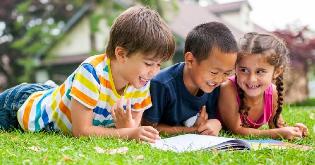 kids laying on grass looking through workbook