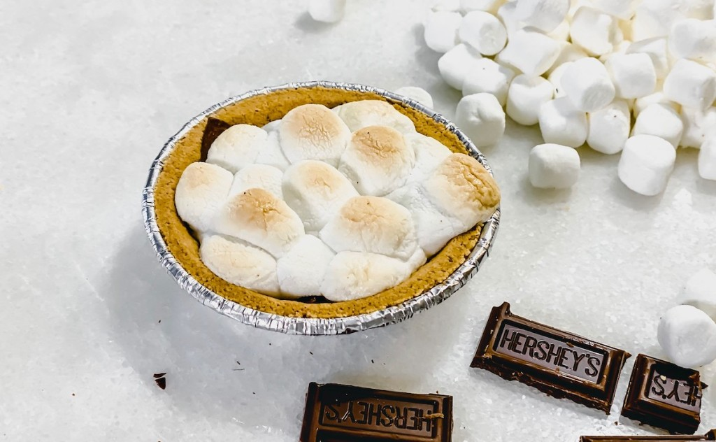 mini smores pie on white counter with hershey's chocolate pieces and mini marshmallows