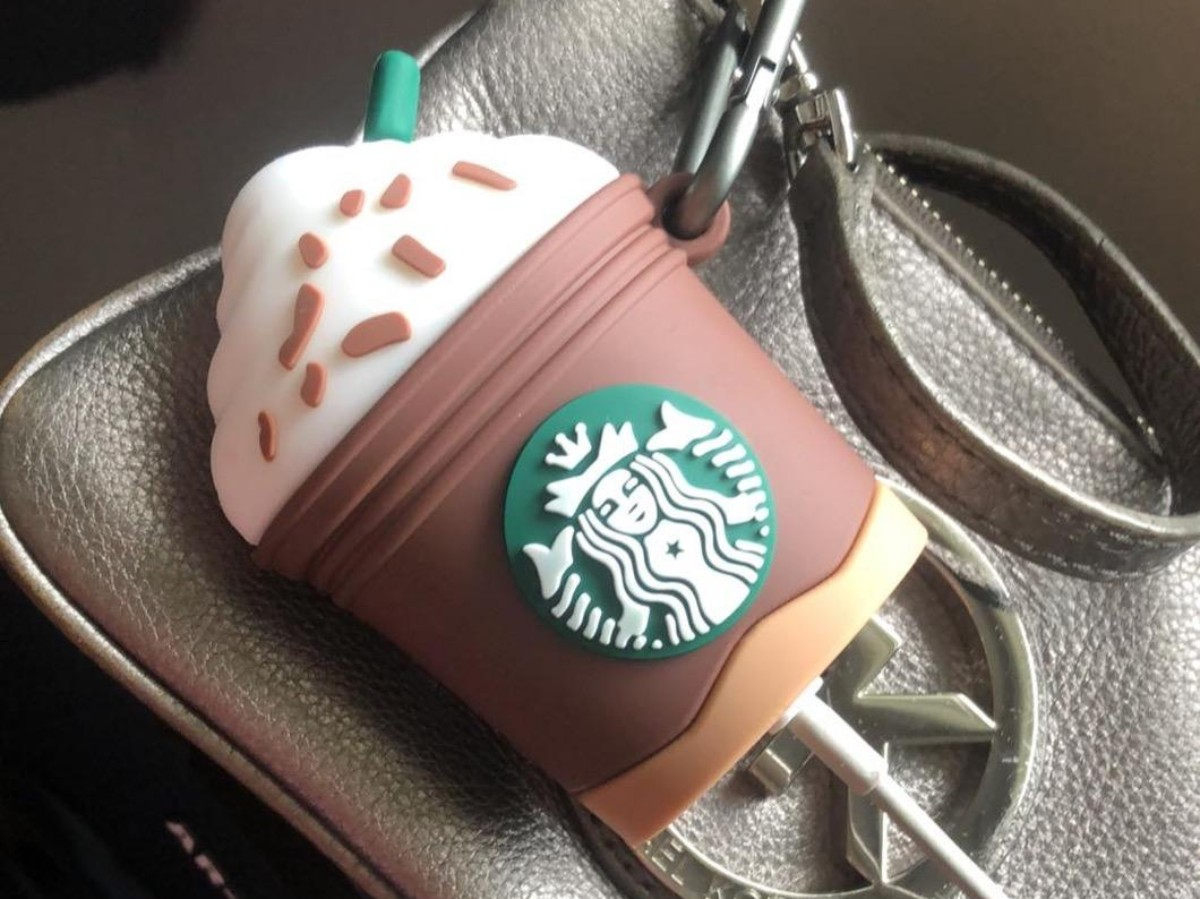 Starbucks Airpods case charging on top of silver purse