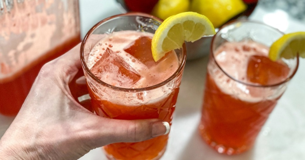 holding strawberry lemonade with lemon wedge