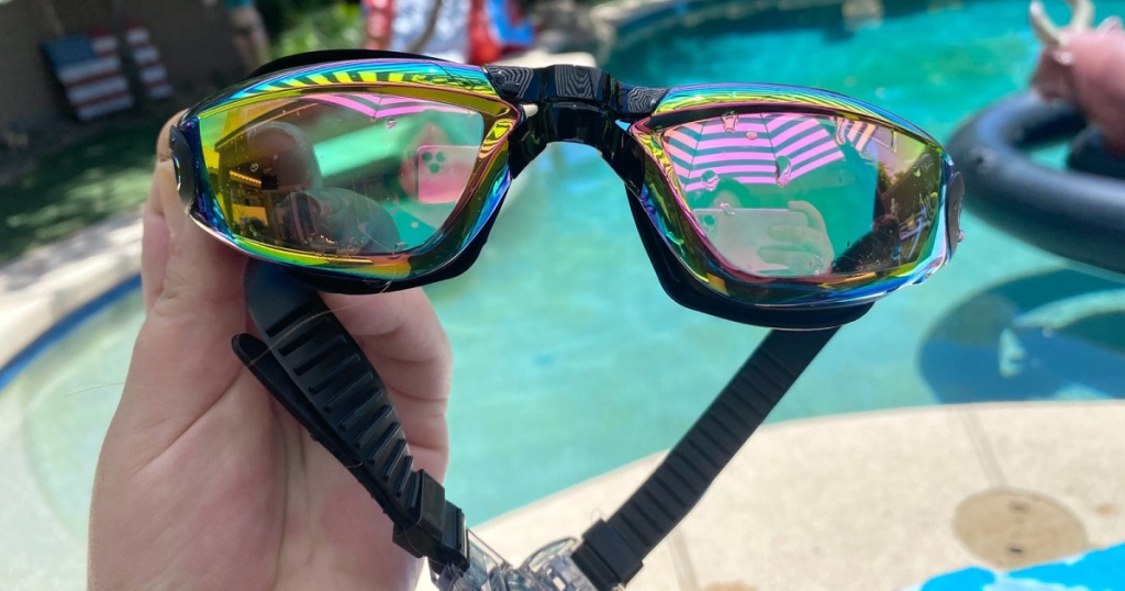 hand holding swim goggles with pool in background
