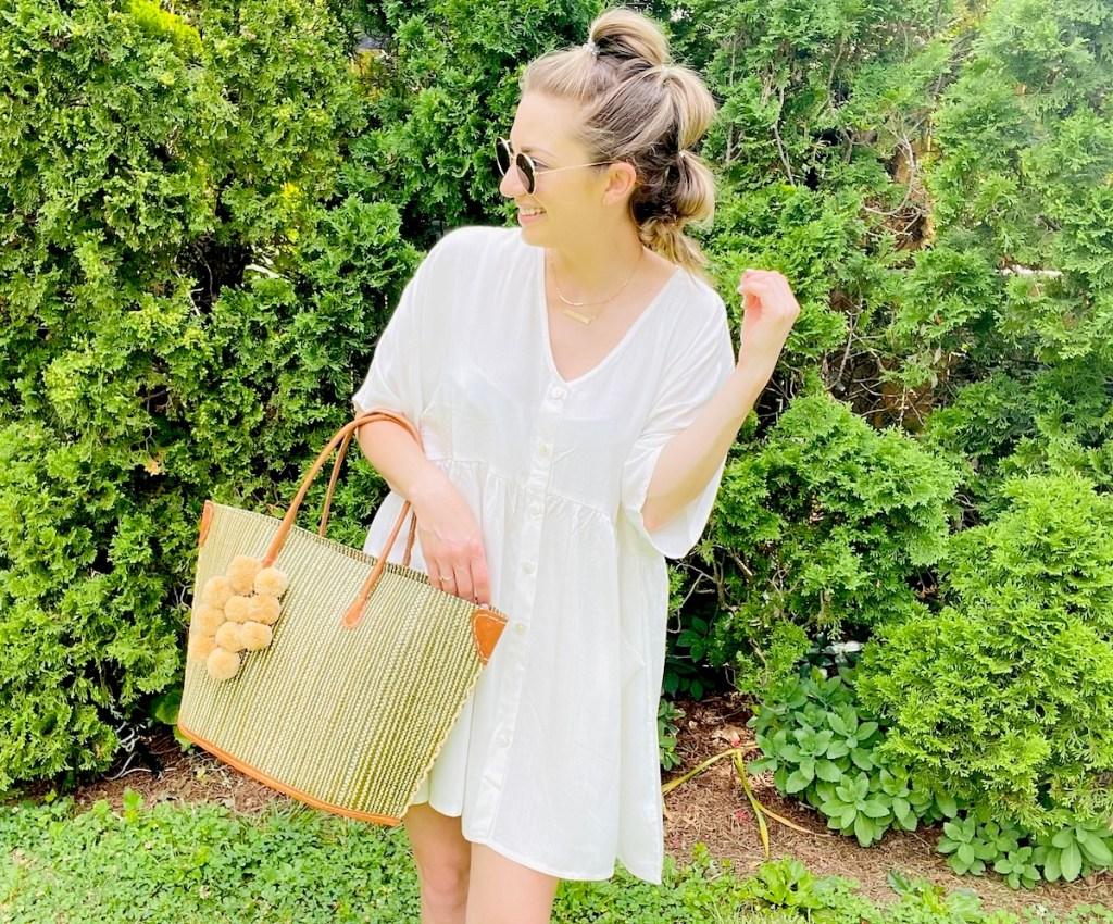 woman wearing white dress holding beach bag outside
