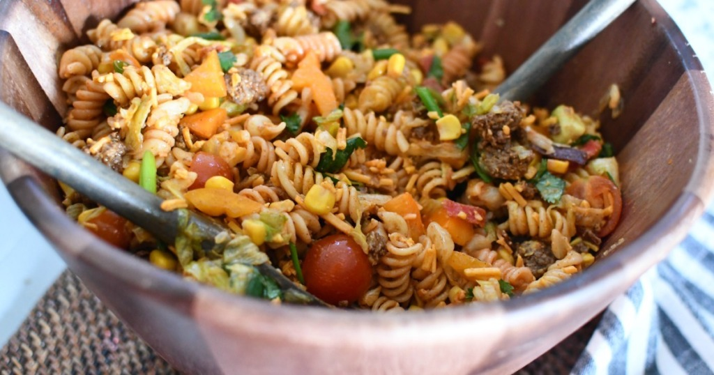 taco pasta salad in wooden bowl with tongs
