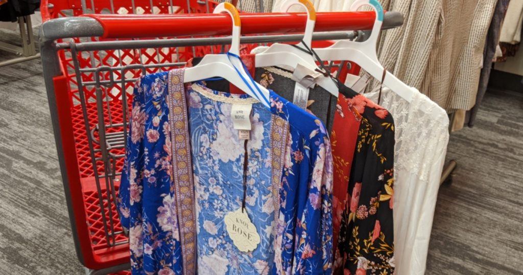 grocery cart with three floral kimonos hanging on it in store