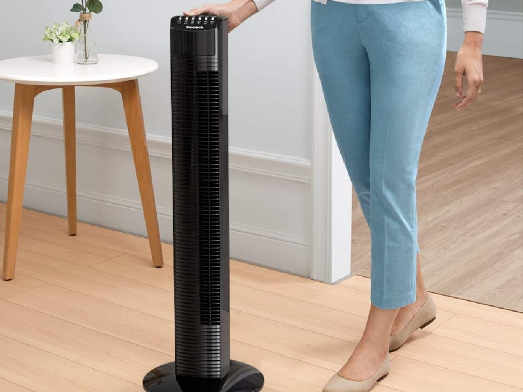 woman touching tall black fan