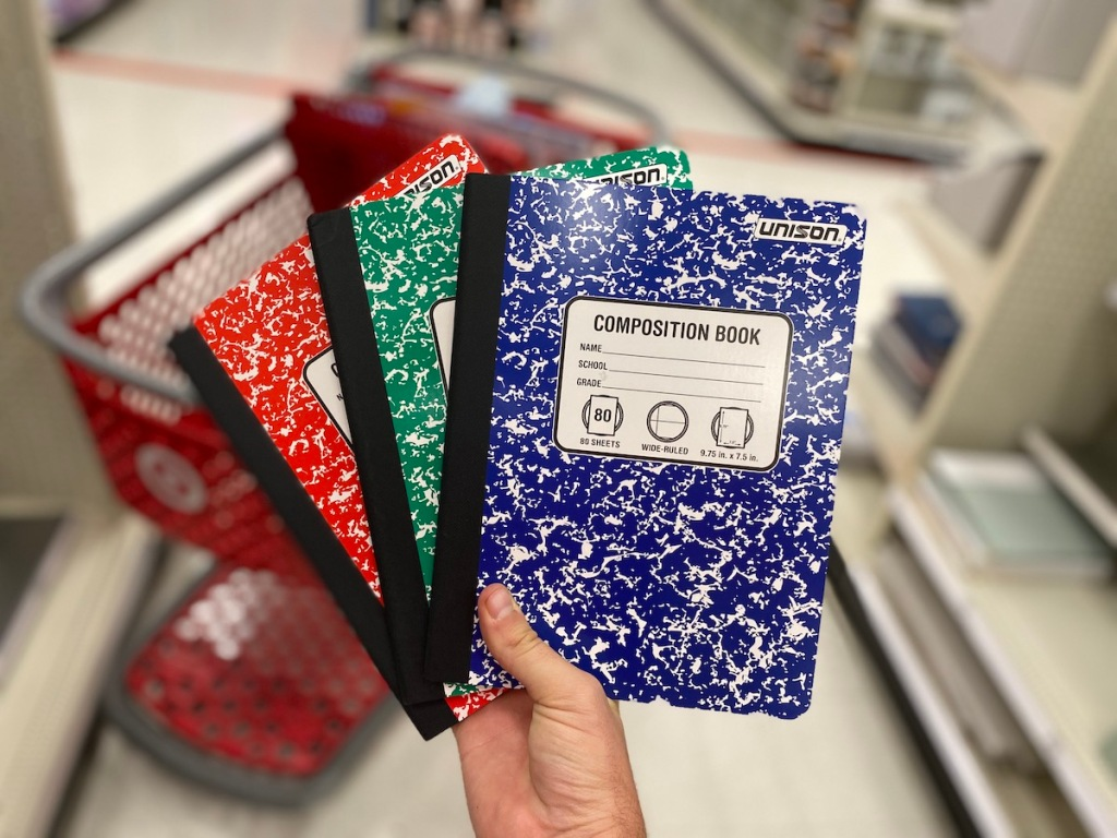 hand holding blue, red, and green colored unison composition books in target aisle